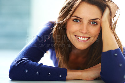 Buy stock photo Pretty happy young lady lying on floor smiling