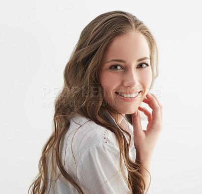 Buy stock photo Studio shot of a young woman looking over her shoulder at the camera