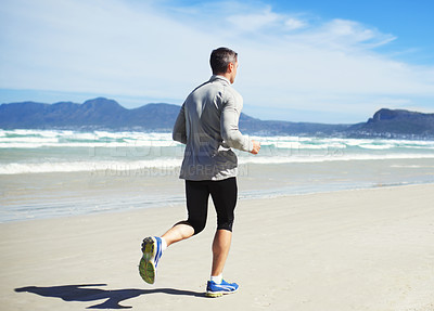 Buy stock photo Rearview shot of a man running along the beach front