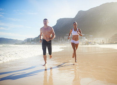 Buy stock photo Full length shot of a couple running along the beach