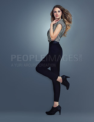 Buy stock photo A studio shot of a trendy young woman isolated on a dark background