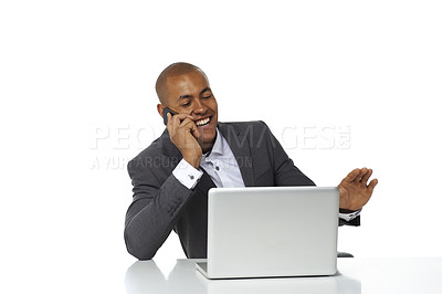 Buy stock photo A handsome young businessman talking on his phone while sitting in front of his laptop