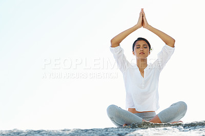 Buy stock photo A young woman performing a yoga routine on the beach in the summer sun