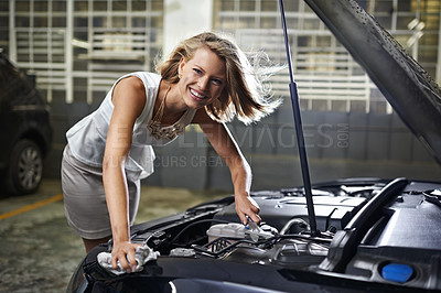 Buy stock photo Portrait of a young woman holding a wrench and smiling confidently with her broken down car