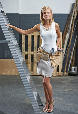 Buy stock photo A stylish young woman wearing a toolbelt in a workshop