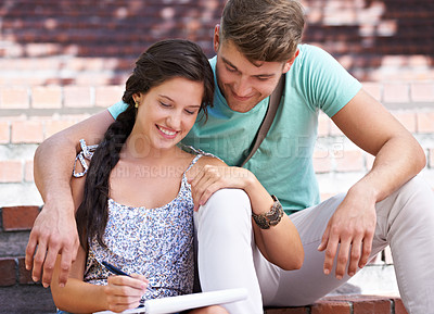 Buy stock photo A young couple studying together on the steps in the park