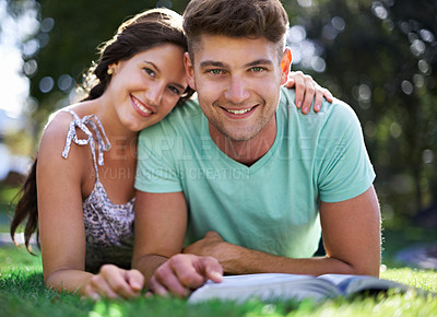 Buy stock photo A young couple in college studying together in the park