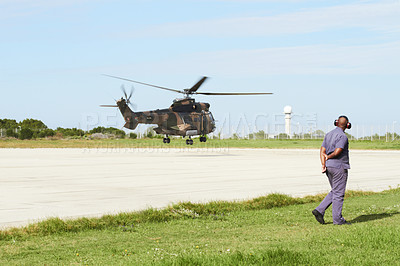 Buy stock photo A helicopter landing on a launchpad while an officer stands on the side
