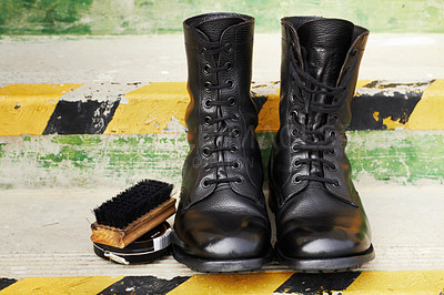 Buy stock photo Shot of a pair of polished army boots sitting on some steps