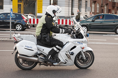 Buy stock photo Shot of a policeman on a motorcycle
