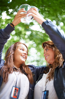 Buy stock photo Two young women enjoying beer together at a festival