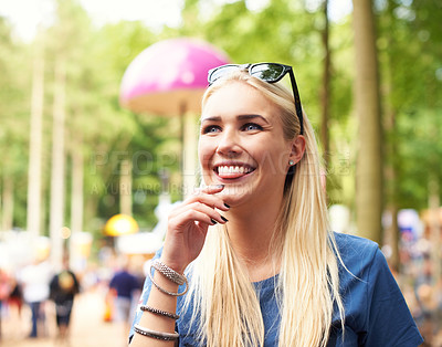 Buy stock photo A beautiful young woman standing outdoors amongst the crowd smiling and looking out of the frame