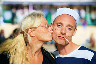 Buy stock photo Shot of a woman kissing a guy in a sailor outfit at a music festival
