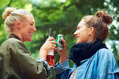 Buy stock photo Shot of two young women having a drink together at an outdoor festival