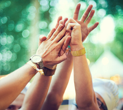 Buy stock photo A group of young people putting their hands together at an outdoor festival
