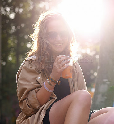 Buy stock photo Portrait of a young woman enjoying a drink outdoors on a sunny day
