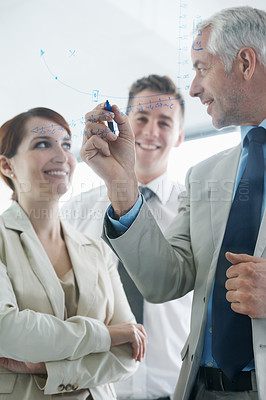 Buy stock photo Shot of businesspeople brainstorming on glass wall in an office