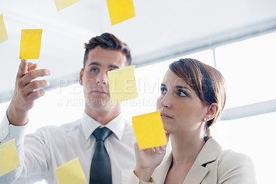 Buy stock photo Shot of a coworkers arranging sticky notes on a glass wall during a brainstorming session