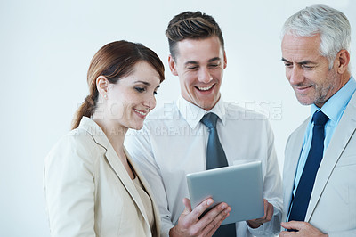 Buy stock photo Shot of a group of smiling business people looking at something on a digital tablet