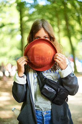 Buy stock photo A young woman standing outside peeking over the rim over her hat