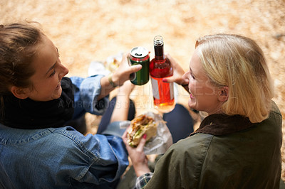 Buy stock photo Two friends enjoy a burger with their wine at a music festival