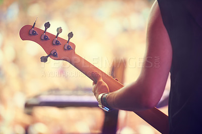 Buy stock photo Cropped shot of a guitarist performing on stage in front of a massive crowd