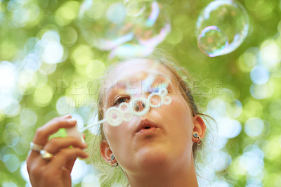 Buy stock photo Cropped shot of a young woman blowing bubbles outside