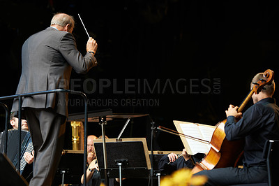 Buy stock photo Shot of a conductor and musicians during an orchestral concert