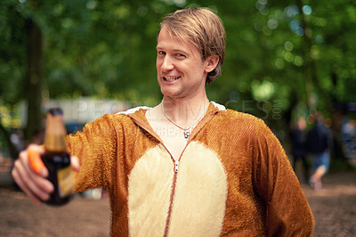 Buy stock photo Portrait of a young man drinking a beer outside while dressed in a bear suit