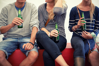Buy stock photo Cropped shot of a group of young adults enjoying beers together