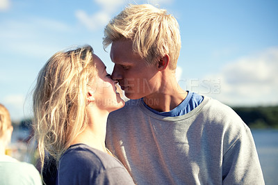 Buy stock photo A young couple kissing outside