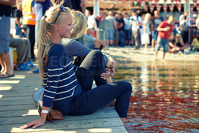 Buy stock photo Shot of two young women dipping their feet into water at an outdoor festival