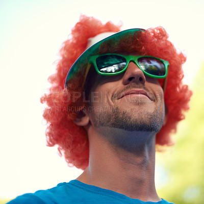 Buy stock photo A young man wearing a playful red wig at an outdoor event