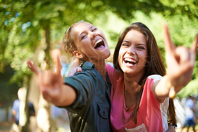 Buy stock photo Two female friends hugging while standing outside