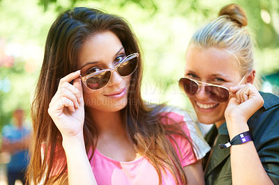 Buy stock photo Two young women glancing over the rim of their sunglasses