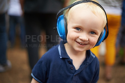 Buy stock photo Closeup shot of a young boy wearing noise canceling headphones at an outdoor festival