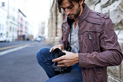 Buy stock photo Shot of a handsome young photographer at work in the city