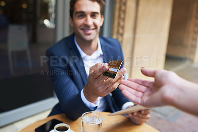 Buy stock photo Young businessman paying for his coffee with a credit card at the cafe