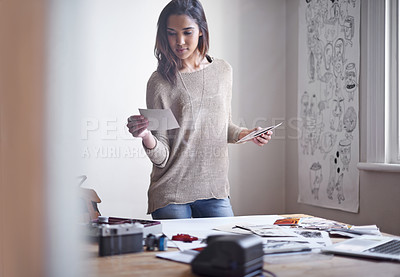 Buy stock photo A young woman selecting pictures to include in her portfolio