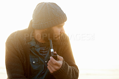 Buy stock photo Cropped shot of a bearded man smoking a pipe outside