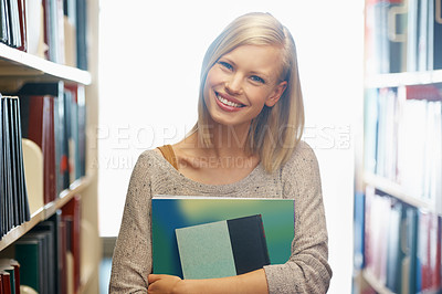 Buy stock photo A young woman holding some books in the library