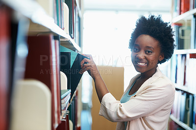 Buy stock photo A young woman selecting some books in the library