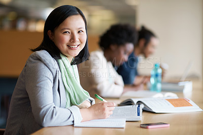Buy stock photo A young woman studying in the library with another students