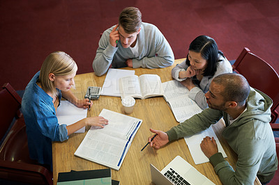 Buy stock photo A group of young people studying together in the library
