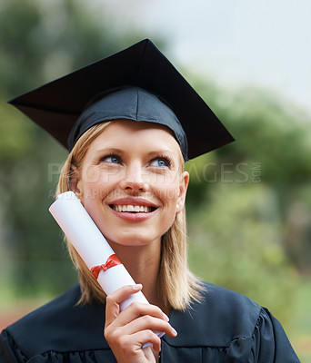 Buy stock photo A young college graduate wearing cap and gown while looking away and smiling