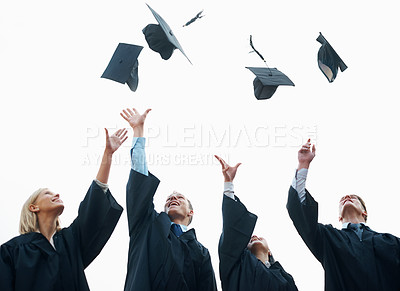 Buy stock photo A group of students throwing their caps into the air after graduation