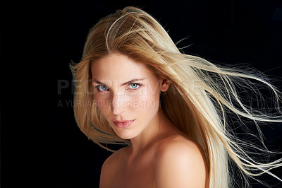 Buy stock photo A beautiful young woman posing in front of a black background with the wind blowing through her hair