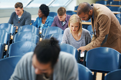 Buy stock photo Shot of a group of college students working on papers in an exam room