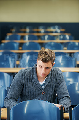 Buy stock photo A young man sitting alone in a lecture hall