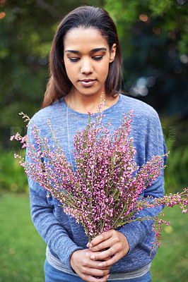 Buy stock photo A young woman holding a bunch of flowers in a garden